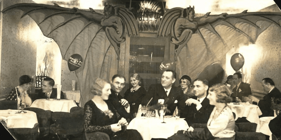 Middle-aged guests sitting and chatting over a drink in a ballroom and restaurant in the 1920s.