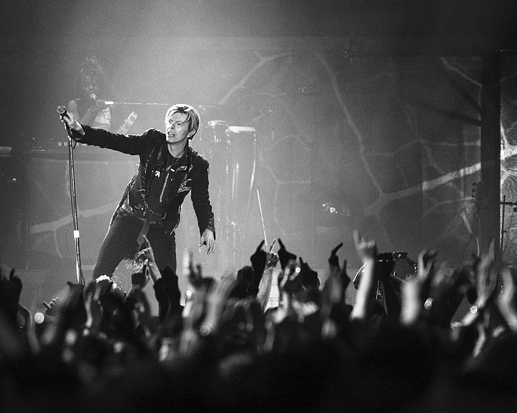 David Bowie performing in front of cheering crowds.